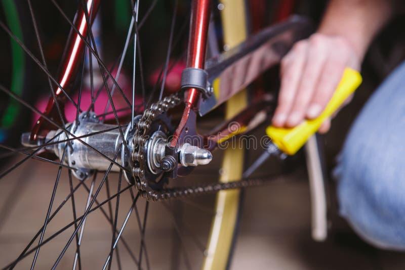 题材修理自行车 一个白种人人` s手用途的特写镜头在一根黄色防喷管的链润滑剂llubricator的自行车cha 库存照片