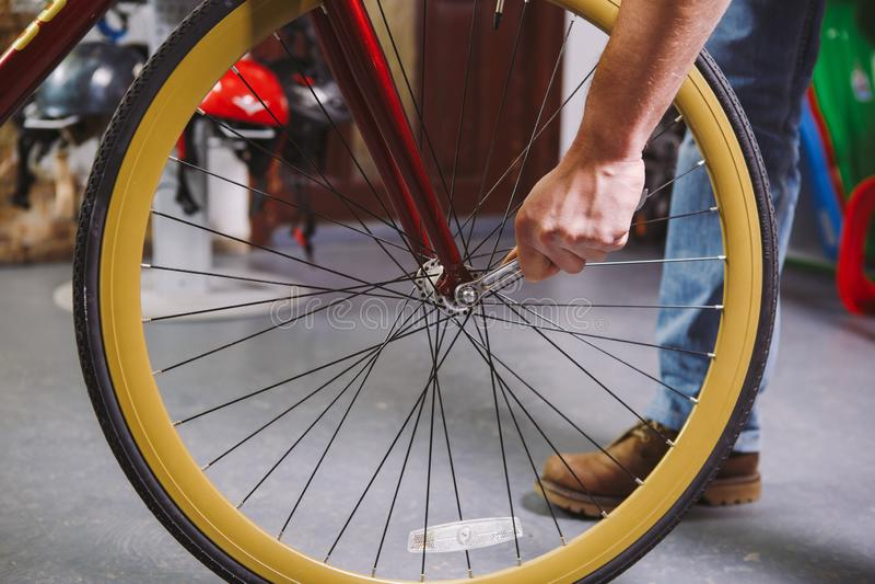 题材修理自行车 一个白种人人` s手用途的特写镜头手工工具自行车用工具加工插孔锥体Wrenc调整和安装 免版税库存照片
