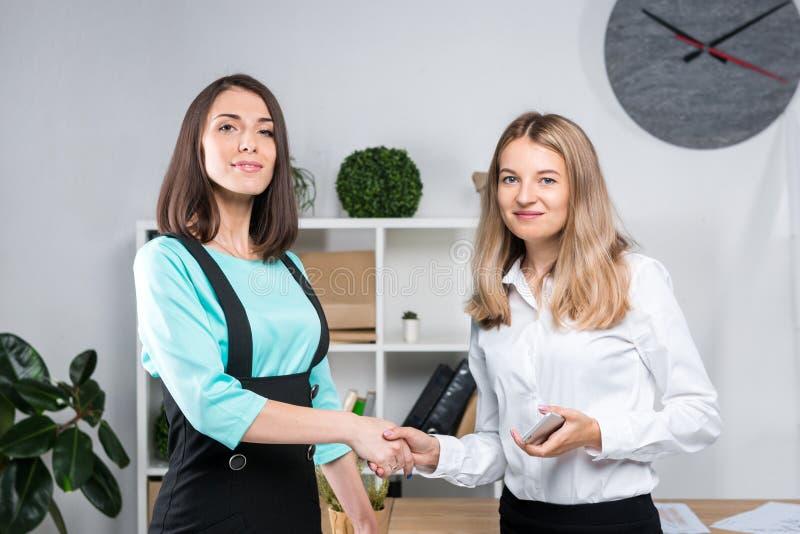 题材女商人 正装的两个年轻白种人妇女商务伙伴签合同,做成交握手  库存图片