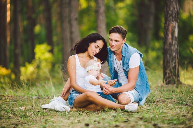 题材家庭室外休闲在森林公园地区 有小孩子的年轻美丽的时髦的白种人家庭 免版税库存照片