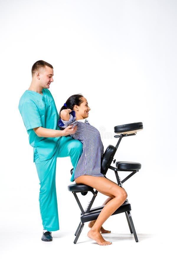 题材按摩和办公室 做与他的膝盖的蓝色衣服的年轻男性治疗师后面按摩支撑在女工脊椎, 免版税库存照片
