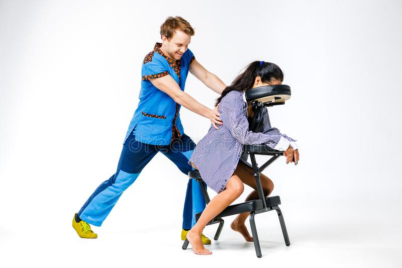 题材按摩和办公室 有微笑的治疗师的一个年轻人蓝色衣服的做着和少妇工作者的, b脖子按摩 图库摄影