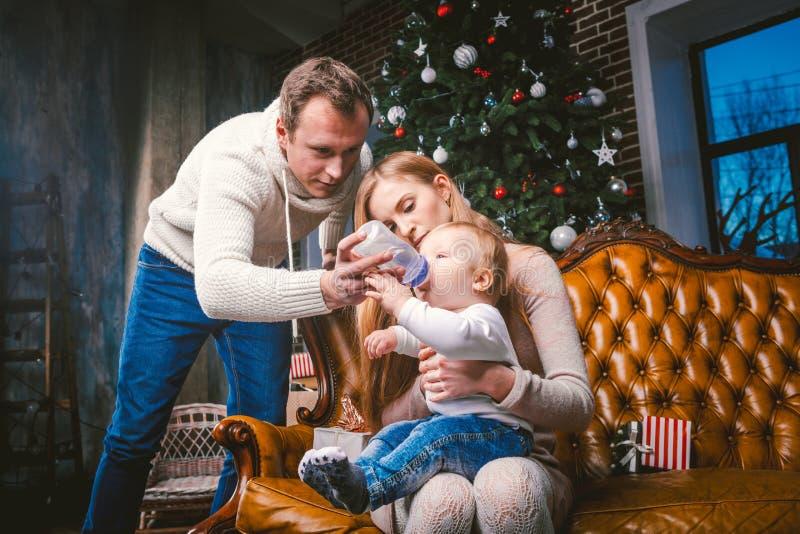 题材新年和圣诞节假日在家庭大气 心情庆祝白种人年轻妈妈爸爸和儿子 父亲哺养 免版税库存照片
