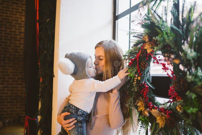 题材新年和圣诞节假日白种人妈妈在窗口附近在家拿着她的胳膊的儿子1年在顶楼内部 免版税库存图片