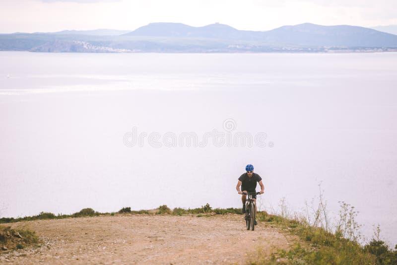 题材旅游业和循环在山骑自行车 人在一条岩石,岩石路乘坐上升以地中海为背景 图库摄影