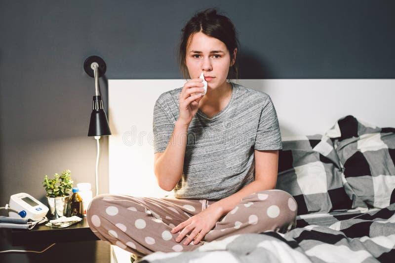 题材是季节性寒冷,鼻涕流感病毒传染 年轻白种人妇女卧室床在家使用药物浪花滴  免版税库存照片