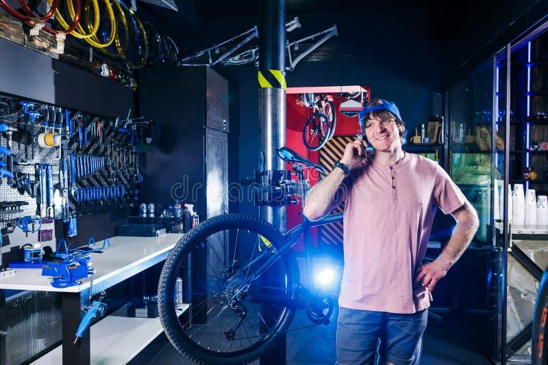 题材是小企业 一个年轻人的画象一个自行车车间的业主自行车修理和维护的  人u 免版税库存图片