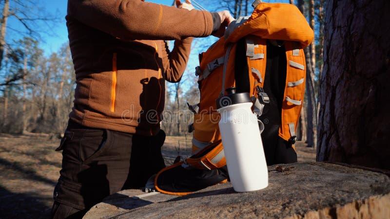 题材暴涨和旅行 一个白种人旅游人在树桩打开橙色背包,去掉他的事并且投入他们在 免版税图库摄影
