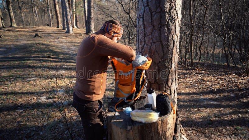 题材暴涨和旅行 一个白种人旅游人在树桩打开橙色背包,去掉他的事并且投入他们在 免版税库存图片