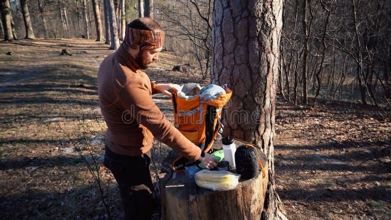 题材暴涨和旅行 一个白种人旅游人在树桩打开橙色背包,去掉他的事并且投入他们在 库存图片