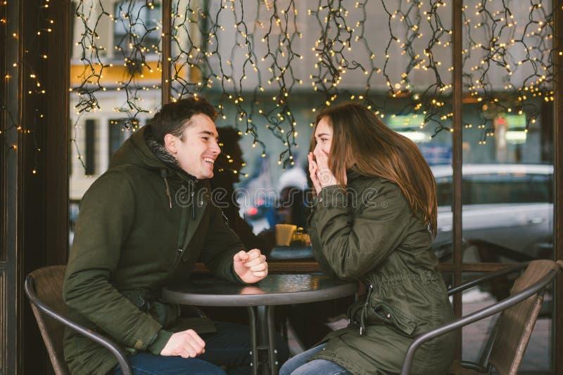 题材爱假日情人节 对大学生,白种人异性爱恋人在冬天,坐街道桌  免版税库存照片