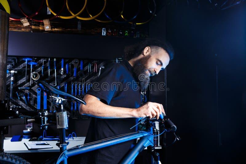 题材自行车销售和修理  年轻和时髦与胡子和长的头发,一个白种人人使用一个工具设定和修理 库存图片