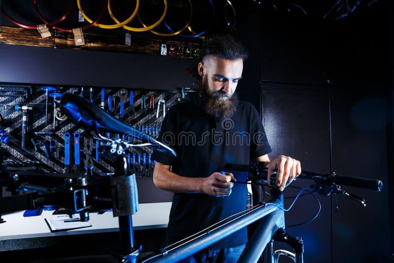题材自行车销售和修理  年轻和时髦与胡子和长的头发,一个白种人人使用一个工具设定和修理 图库摄影