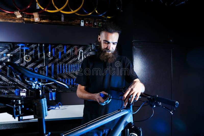 题材自行车销售和修理  年轻和时髦与胡子和长的头发,一个白种人人使用一个工具设定和修理 库存照片