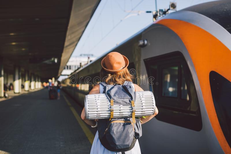 题材运输和旅行 在火车站平台的年轻白种人妇女身分在火车附近支持火车背景与 免版税库存图片