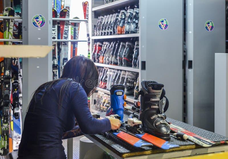 题材酊修理滑雪设备滑雪 一个白种人妇女` s手用途的特写镜头一件手提式螺丝刀工具扭捏,扭转双 库存照片