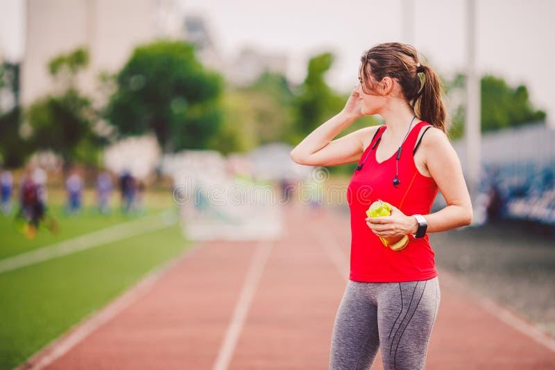 题目是体育和健康 使用一个手机,训练的一名年轻白种人妇女在运动服谈话,手是耳朵 库存照片