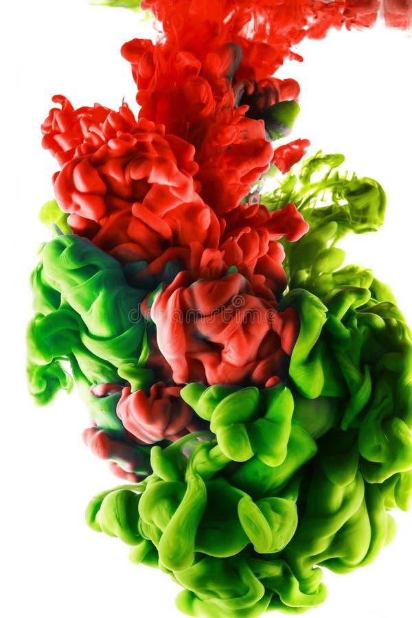 颜色下落 在白色背景的红色和绿色墨水 免版税库存图片