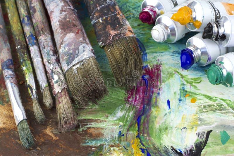 绘颜色和刷子在艺术家调色板 免版税图库摄影