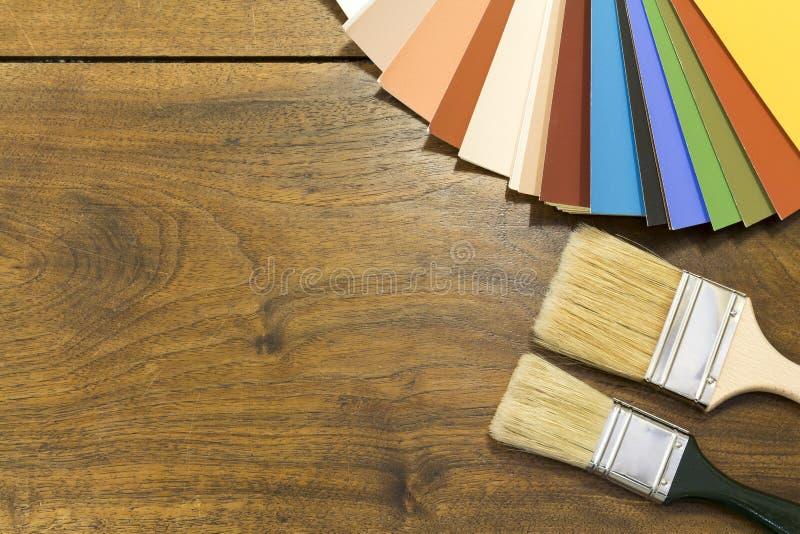 颜色图表和刷子在木背景 免版税库存照片