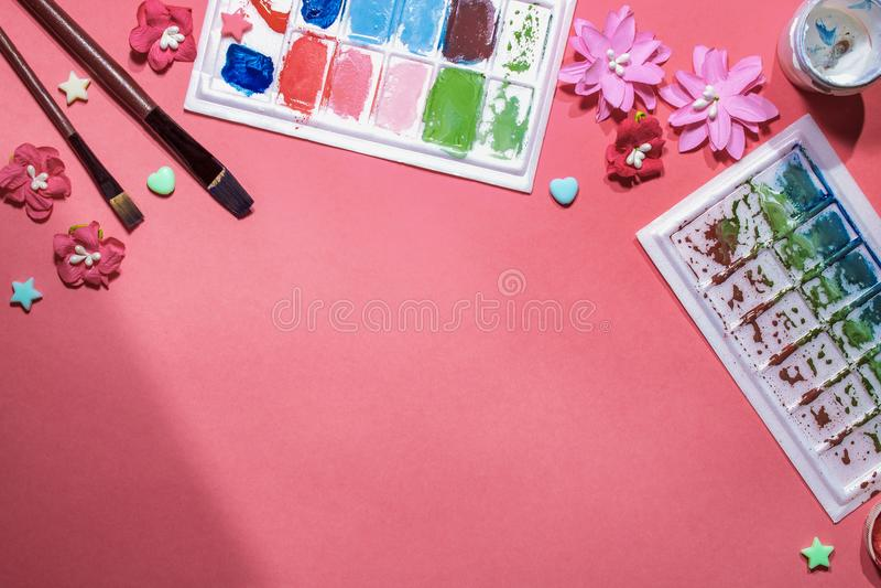 颜色在桃红色背景的树胶水彩画颜料瓶子 顶视图,拷贝空间 免版税库存照片