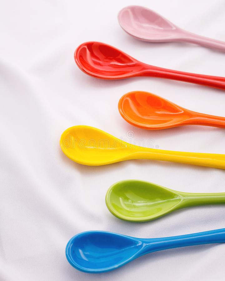 颜色在白色织品背景的陶瓷匙子 五颜六色的概念 免版税库存图片