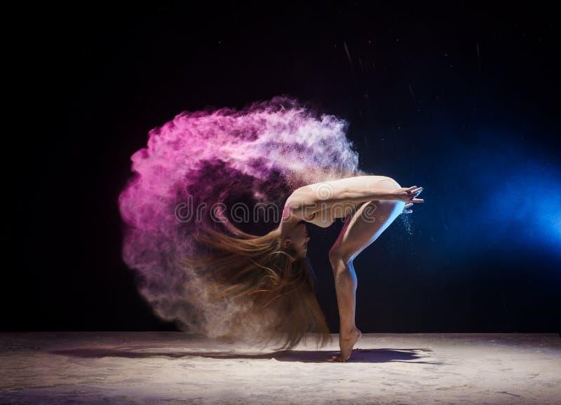 颜色尘土云彩的优美的女性体操运动员  免版税库存照片