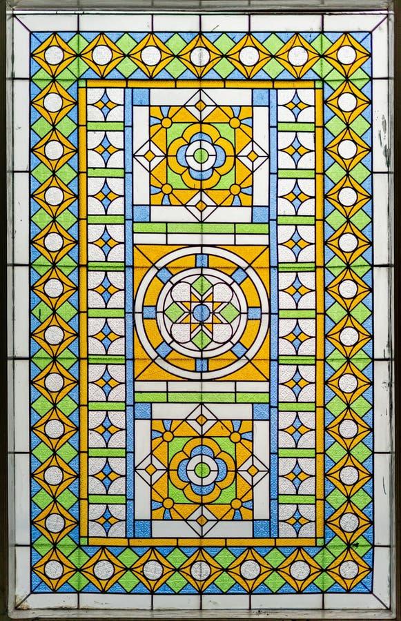 颜色彩色玻璃在窗口 明亮的五颜六色的经典之作蓝绿色橙色玻璃纹理和背景 免版税库存图片