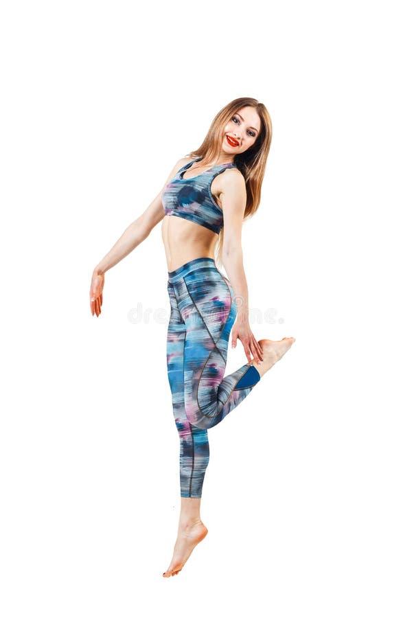 颜色蓝色上面和绑腿跳跃的年轻美丽的妇女喜悦 在白色背景隔绝的年轻运动的适合emale模型  免版税库存照片