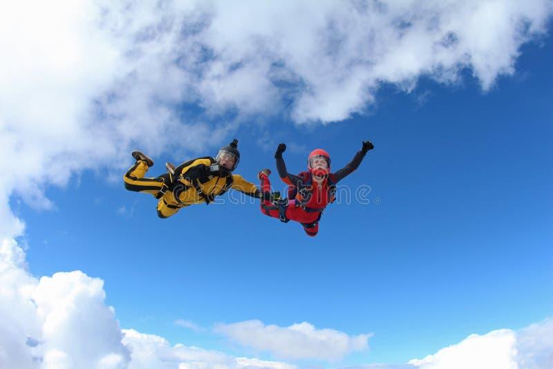 颜色衣服的两个跳伞运动员在云彩跌倒 库存照片