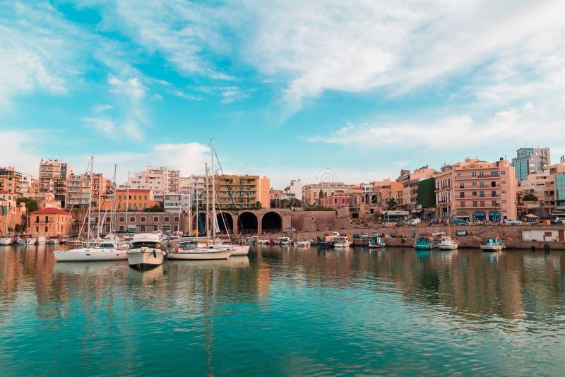 颜色转移了伊拉克利翁市旧港口全景海漂浮和建立葡萄酒神色的天空小船照片  免版税库存照片