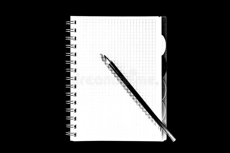 颜色铅笔和笔记本,在黑背景的孤立,黑白照片 免版税库存图片