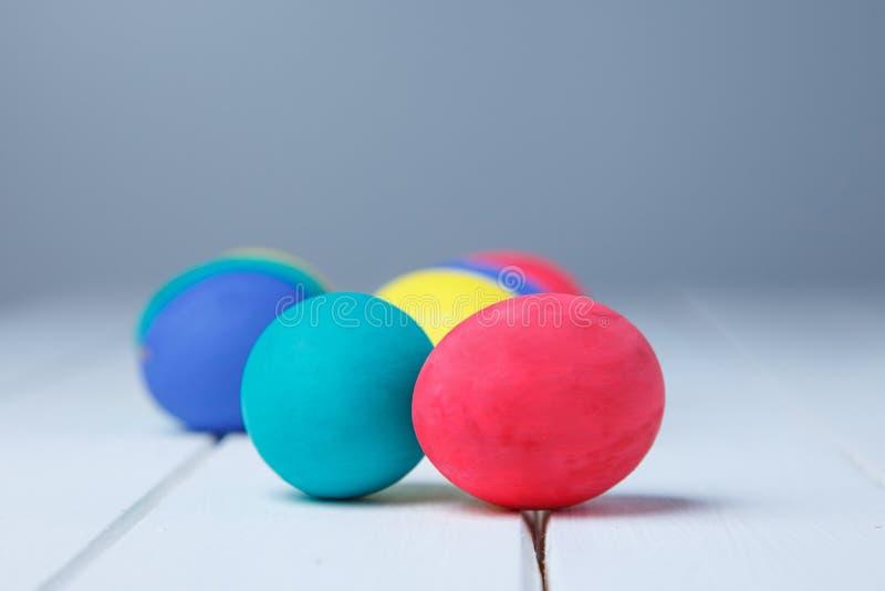 颜色鸡蛋在白色桌里 愉快的复活节 库存图片