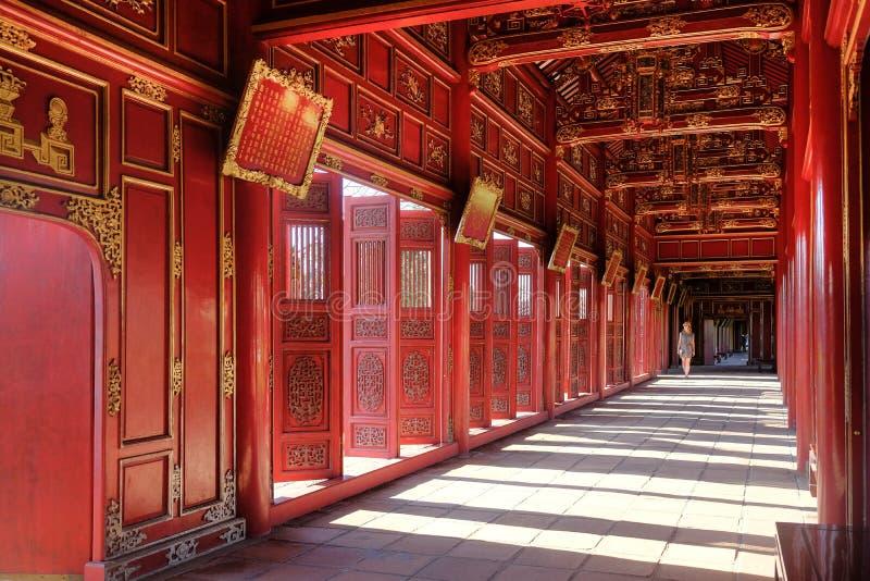 颜色/越南,17/11/2017:穿过在城堡复合体的一红色装饰pavillion的妇女在颜色,越南 免版税库存照片