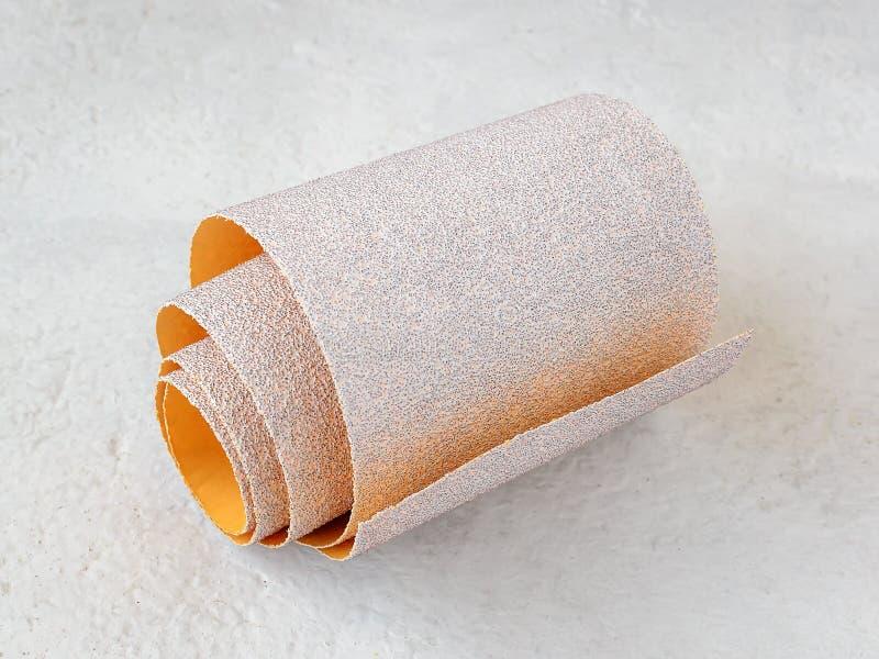 额外粗糙的氧化铝沙纸一小卷在白色质感粗糙的背景的 烘干沙的砂纸 免版税库存照片