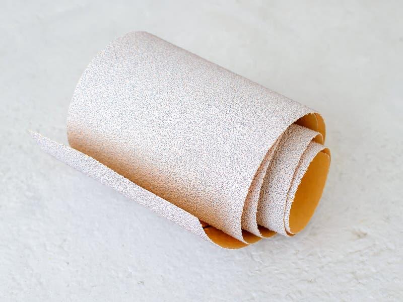 额外粗糙的氧化铝沙纸小卷在白色质感粗糙的背景的 烘干沙的砂纸 库存图片