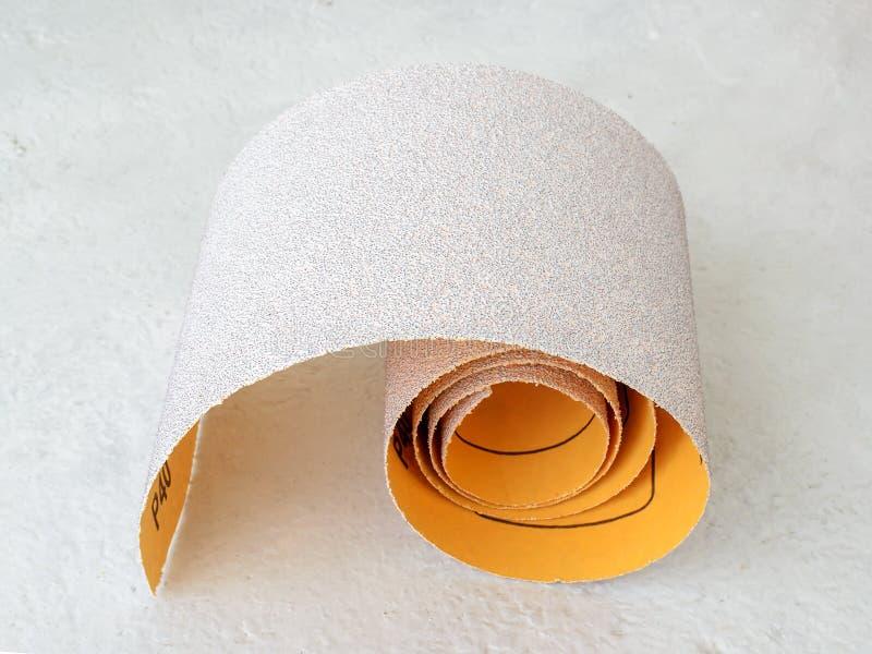 额外粗糙的氧化铝沙纸小卷  烘干沙的砂纸 处理木头和金属,家具 免版税库存照片