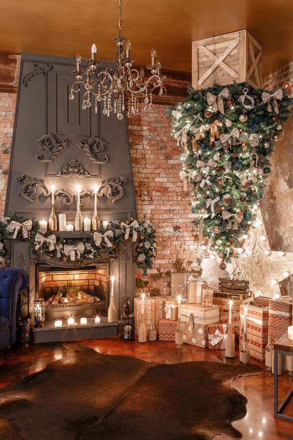 颠倒供选择的树在天花板 浆果装饰霍莉家留给槲寄生多雪的结构树白色冬天 与壁炉和砖墙的现代顶楼内部 免版税库存图片