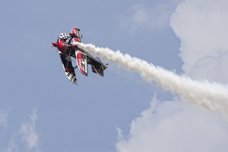 颠倒双翼飞机在多云天空 免版税库存照片