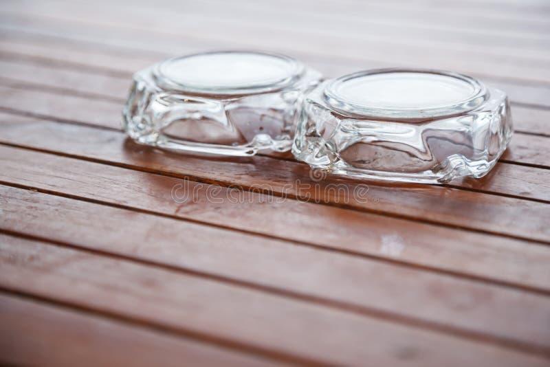 颠倒未使用的玻璃烟灰缸在木桌或长凳上在阳台 吸烟区的内部家具装饰设计  图库摄影
