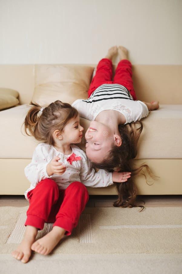 颠倒长沙发的小逗人喜爱的女孩 免版税库存照片