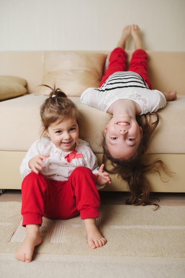 颠倒长沙发的小逗人喜爱的女孩 库存照片