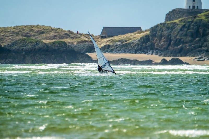 风冲浪者在有Llanddwyn, Anglesey小岛海岛的Newborough沃伦在背景中享用海滩  库存照片