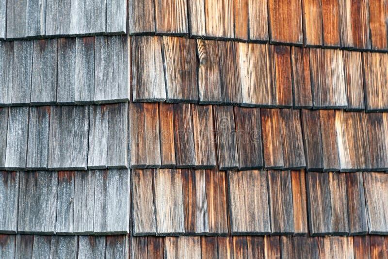 风化和从是一个高山房子的门面的太阳木木瓦退了色 木纹理在树荫下灰色和 库存图片