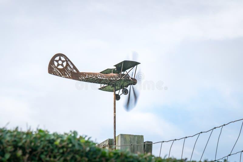 风向以一架老生锈的双翼飞机的形式,在一个边看法,与推进器移动 免版税库存图片