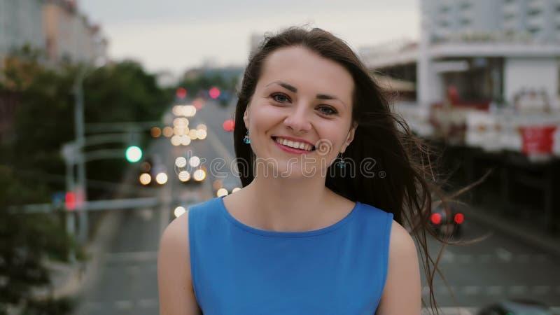 风吹长的黑发美丽的少妇 愉快,微笑的女孩站立在桥梁的和神色在照相机 4K 免版税图库摄影