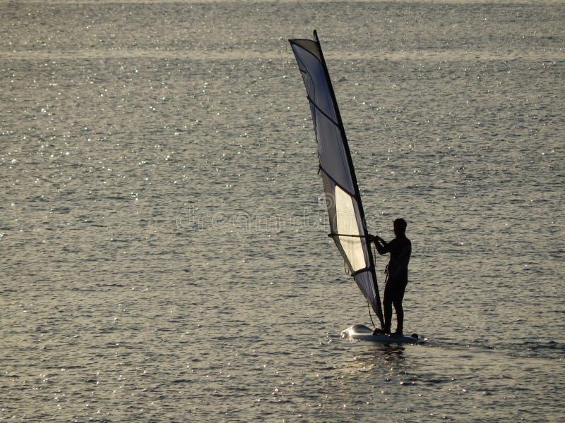 风帆冲浪与日落光 免版税库存图片