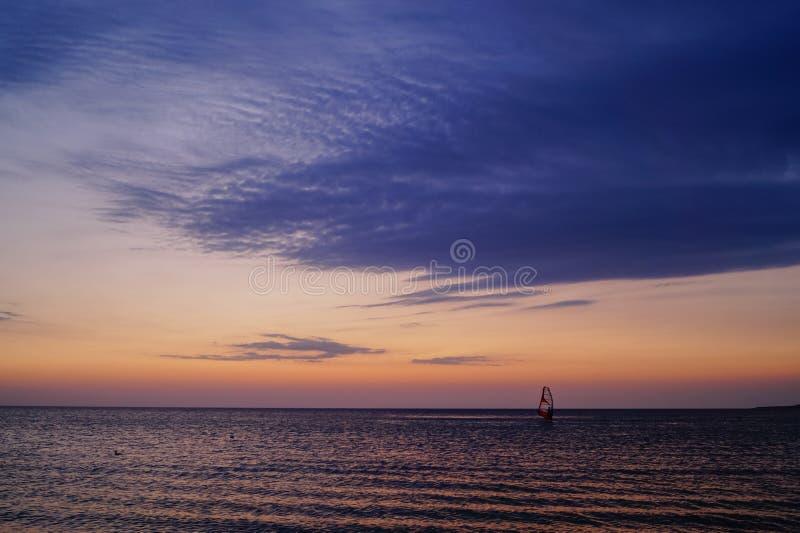 风帆冲浪在日落在海 免版税库存图片