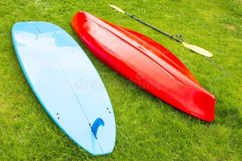 风帆冲浪小船,并且有桨的皮船在草放置 库存图片