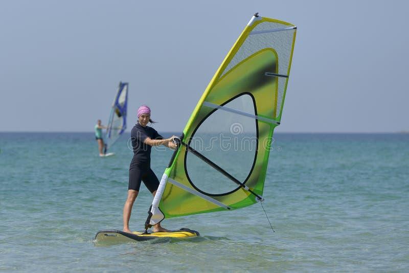 风帆冲浪海上的年轻体育妇女在一好日子 免版税库存照片